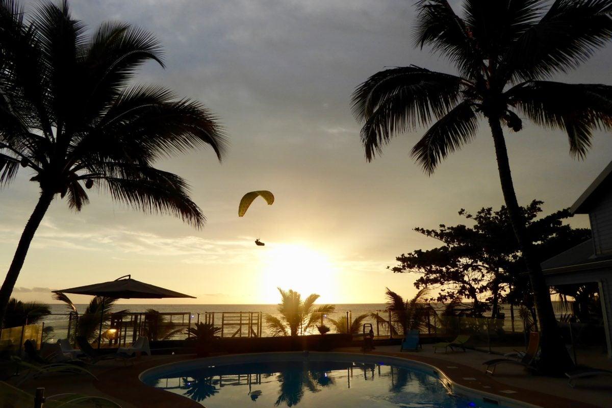 Gleitschirmreise La Reunion Schirm zwischen Palmen im Sonnenuntergang