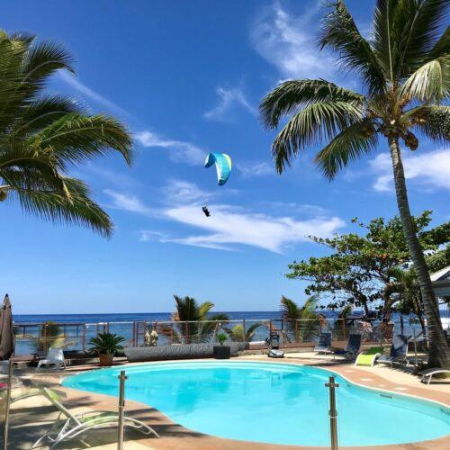 Gleitschirmreise La Reunion Schirm zwischen Palmen und Pool im Landeanflug