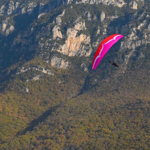 Ozone Alpina 3 rosa im Flug von schräg oben über Landschaft